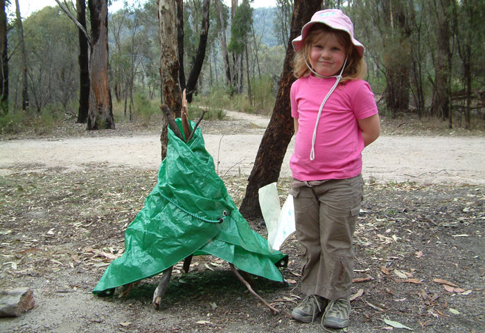Savanna proudly showing off the teepee she built from sticks, a tarp and a bungee cord